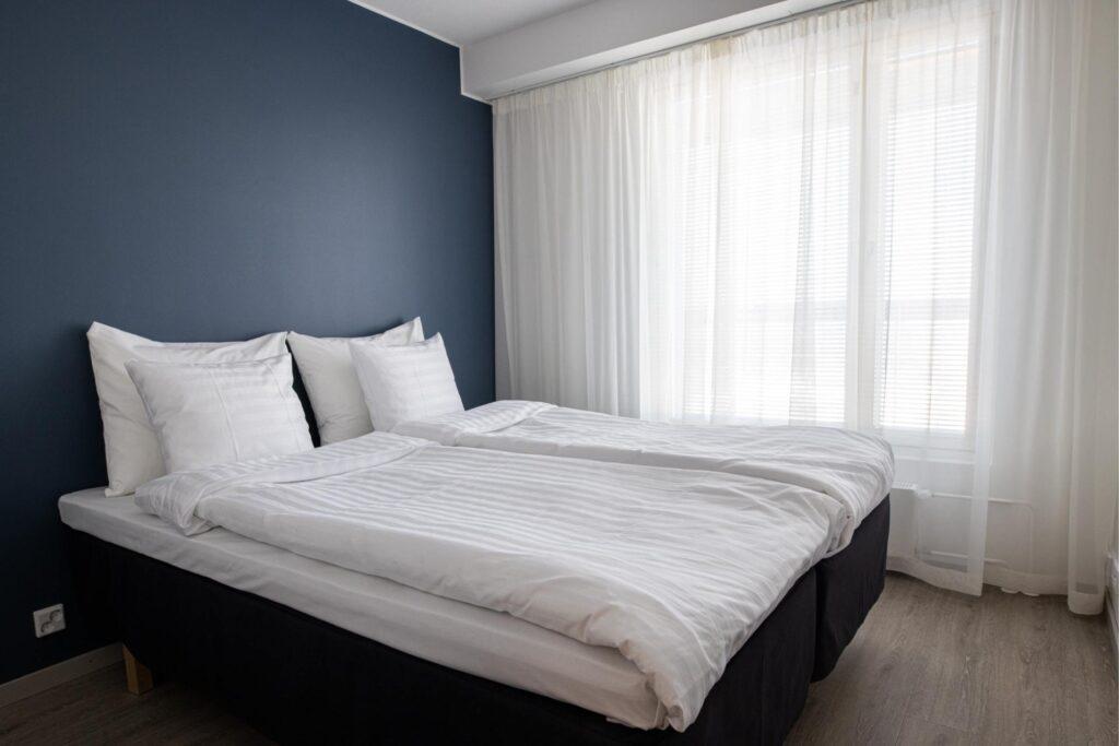 Rauhallisen sävyinen makuuhuone Hotel Mattsin kaksiossa.