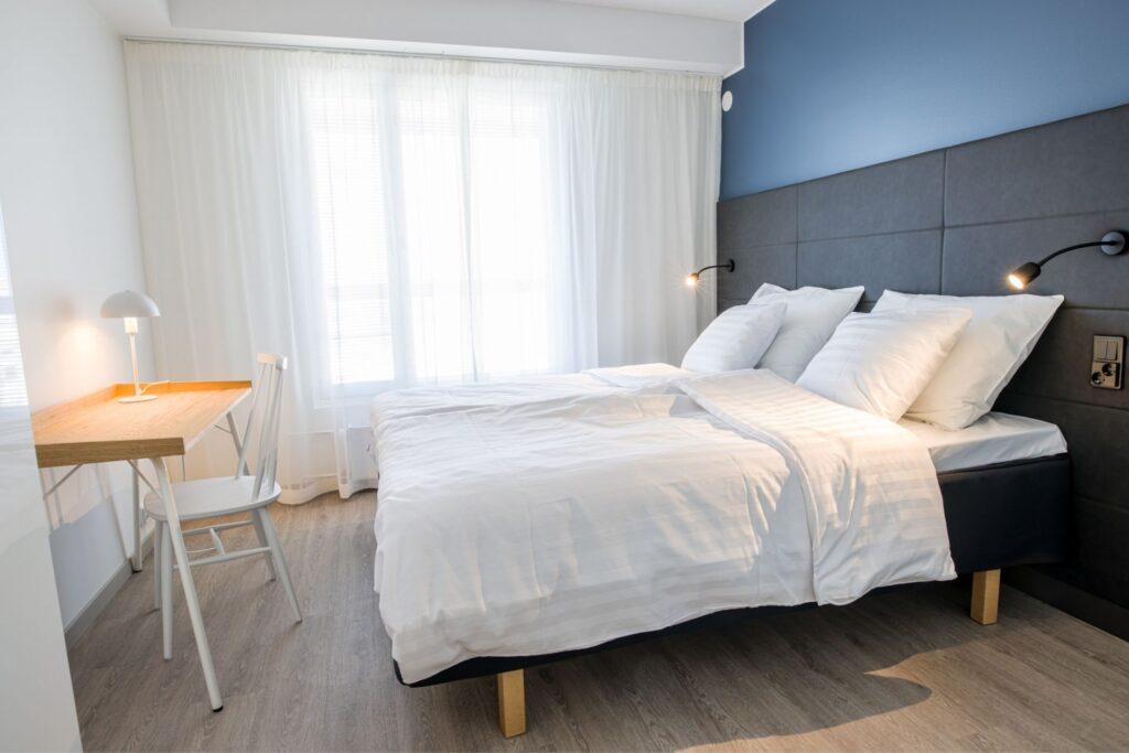 Viihtyisä makuuhuone suurella sängyllä ja värikkäillä tyynyillä huoneistohotelli Hotel Mattsissa Espoossa.