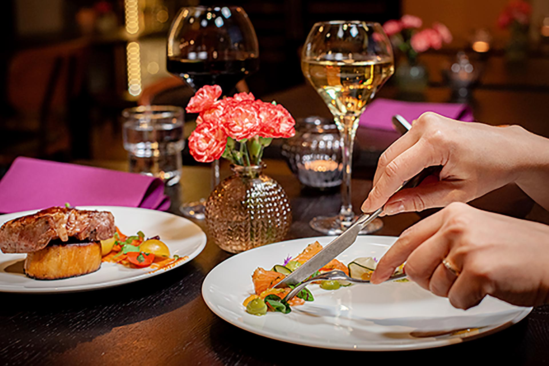 Värikäs alkuruoka, pääruoka ja viinilasit tunnelmallisessa ravintolassa Espoossa.