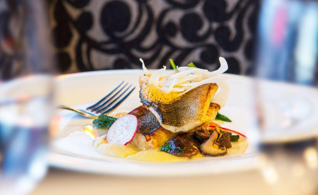Näyttävä kala-annos ja viinilasit Hotel Mattsin juhlatilassa Espoon Matinkylässä.