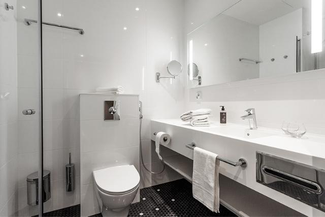 Espoon Hotel Mattsin Standard hotellihuoneen valoisa ja tilava kylpyhuone.