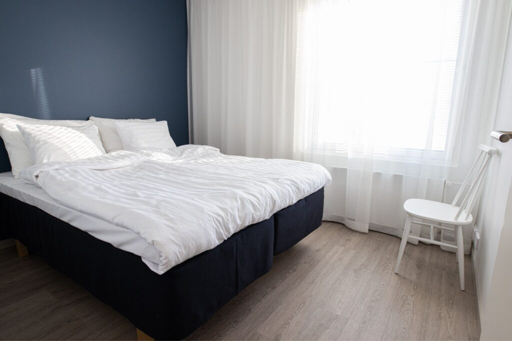 Rauhallisen sävyinen makuuhuone Hotel Mattsin neliössä.