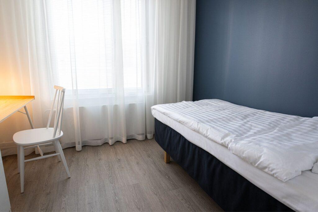 Rauhallisen sävyinen yhden hengen makuuhuone Hotel Mattsin neliössä.