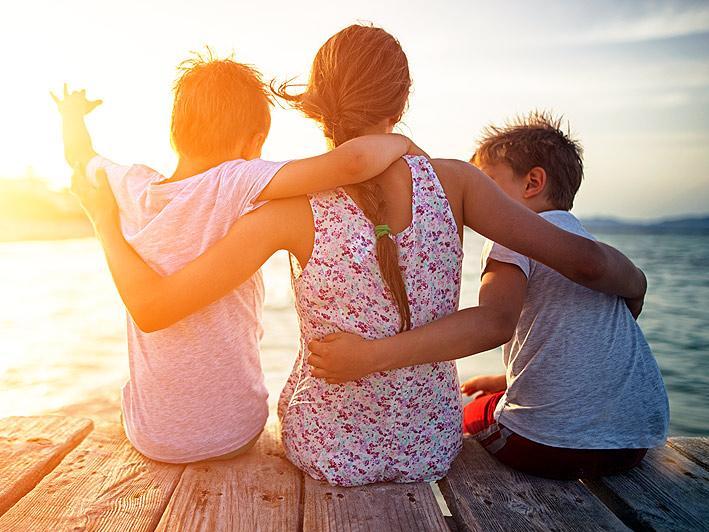 Perhe istuu merenrannalla auringonlaskussa Espoossa.