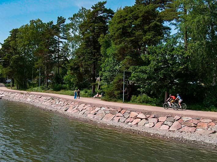 Pyöräilijät Espoon Rantaraitilla meren äärellä.